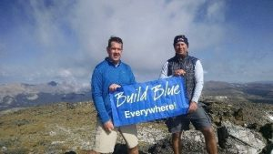 men holding build blue banner on top of a mountain